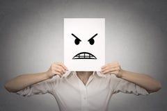 盖她的面孔的女实业家用恼怒的面具 免版税图库摄影