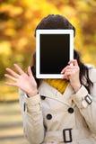 盖她的面孔的妇女用数字式片剂屏幕 图库摄影