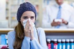 盖她的鼻子的顾客,当打喷嚏在药房时 免版税图库摄影