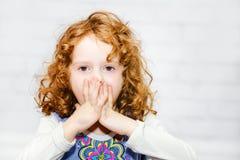 盖她的嘴的小女孩用她的手 免版税库存图片