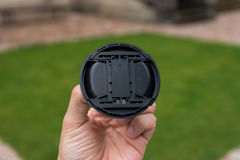 盖子透镜在一只白色手上 免版税图库摄影