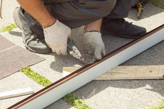 盖屋顶的人削减在金属剪刀的外形 库存图片