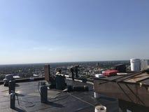 盖屋顶的人和工作在一个光滑的修改过的屋顶平台的乘员组,顶房顶过程中的项目 免版税库存图片