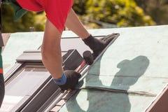 盖屋顶的人在与橡胶短槌的一个屋顶窗口安装金属外形 库存照片