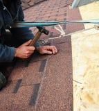 盖屋顶的人安装沥清与锤子和钉子的屋顶木瓦 屋顶 免版税库存图片