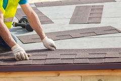 盖屋顶的人安装沥青木瓦或沥清瓦片的建造者工作者在一个新房建设中 免版税库存图片