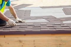 盖屋顶的人安装沥青木瓦或沥清瓦片的建造者工作者在一个新房建设中 库存照片
