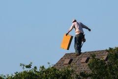 盖屋顶的人工作在峰顶走 免版税库存照片