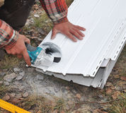 盖屋顶的人工作者使用一个电工具以砂轮切开下端背面到顶房顶房子 免版税库存照片