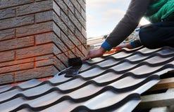 盖屋顶的人建造者工作者附上对烟囱的金属板 未完成的屋顶建筑 免版税库存图片