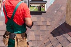 盖屋顶的人有安装屋顶木瓦的袋子的建造者工作者工具 库存照片