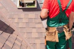 盖屋顶的人有安装屋顶木瓦的袋子的建造者工作者工具 免版税库存照片