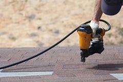 盖屋顶的人有安装沥青木瓦或沥清瓦片的nailgun的建造者工作者在一个新房建设中 库存图片