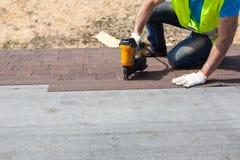 盖屋顶的人有安装沥青木瓦或沥清瓦片的nailgun的建造者工作者在一个新房建设中 免版税库存照片