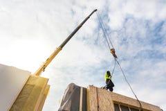 盖屋顶的人有安装结构被绝缘的盘区SIP的起重机的建造者工作者 修造的新的框架省能源的房子 免版税库存图片
