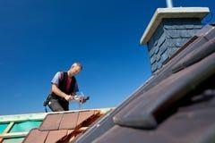 盖屋顶的人有锤子的造型瓦片 库存图片