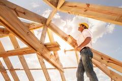 盖屋顶的人,运作在大厦屋顶结构的建造者在建造场所的 免版税库存图片