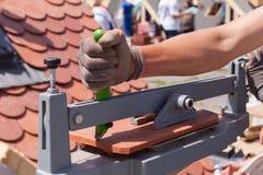 盖屋顶的人建造者工作者用途创造自然红色陶瓷砖的正确大小的瓷砖刀 免版税库存照片