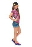 盖帽、衬衣和牛仔布短裤的时髦的女孩 街道样式少年,生活方式,隔绝在白色背景 库存照片