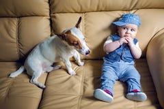 盖帽、裤子、领带和背心的快乐男孩孩子金发碧眼的女人坐 免版税图库摄影