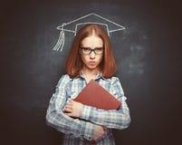 盖帽、玻璃和一本书的学生女孩在黑板 免版税库存图片