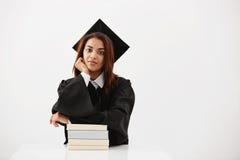 盖帽和披风微笑的坐的非洲女性毕业生与在白色背景的书 免版税库存图片
