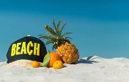 盖帽和果子在一个热带海滩 免版税库存图片