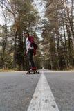 盖帽和格子花呢上衣的一个年轻行家在一条乡下公路乘坐他的longboard在森林里 免版税库存照片