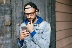 盖帽和牛仔布夹克的严肃的被集中的有胡子的人站立对破裂的墙壁拿着智能手机喜欢岗位和分享的 免版税库存照片