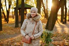 盖帽和米黄夹克的微笑的上午迷人的逗人喜爱和舒适女孩 免版税库存照片