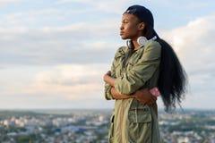 盖帽和耳机的逗人喜爱的非裔美国人的女孩周道地看  被弄脏的都市风景背景 库存照片