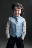 盖帽和蓝色背心的小男孩 免版税库存图片