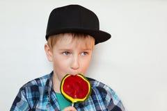 黑盖帽和被检查的衬衣的吃一个明亮的棒棒糖的一个逗人喜爱的矮小的白肤金发的男孩的画象被隔绝在白色背景looki 图库摄影