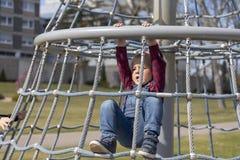 盖帽攀登的小男孩在公园的密林健身房 库存照片