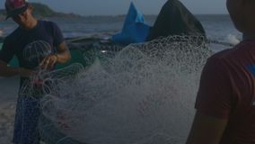 盖帽检查捕鱼网的人在海滩的风暴以后 影视素材