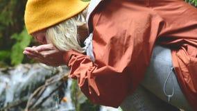 盖帽的一个俏丽的女孩旅客坐一条山小河的银行在一个具球果森林里并且喝清楚的水 影视素材