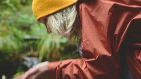 盖帽的一个俏丽的女孩旅客坐一条山小河的银行在一个具球果森林里并且喝清楚的水 股票录像