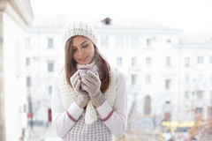 盖帽的一个女孩在有一杯咖啡的街道上站立 库存图片
