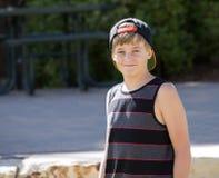 盖帽的一个愉快的十几岁的男孩为画象微笑 免版税库存图片