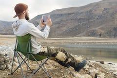 盖帽的一个有胡子的行家坐在一个高山湖的岸的一把折叠椅并且拍在片剂的一张照片 A 免版税库存照片