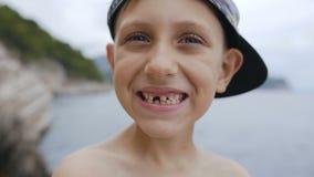 盖帽的一个逗人喜爱的无牙的男孩在照相机微笑着对海背景 微笑男小学生的画象没有牙的 股票录像