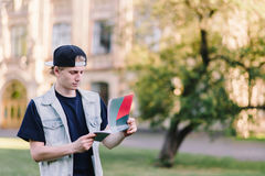 盖帽的一名被集中的学生在大学的背景读从他的笔记本的任务 库存照片