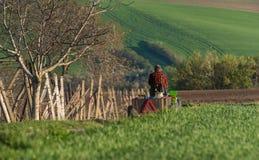 盖帽的人和沿路的红色方格的衬衣乘驾在一台小拖拉机的一个绿色春天领域中,装载用工具和Var 免版税库存照片