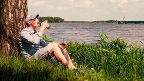 盖帽的人在树下坐湖和饮料水岸  股票视频