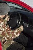 盖帽的人在汽车的燃烧投入钥匙 库存照片