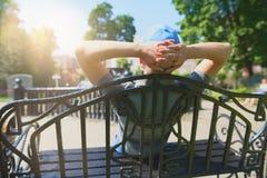盖帽的人坐与他的长凳  免版税库存图片