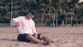 盖帽的人坐并且倾倒在海洋岸之上的沙子在早黄昏 股票视频