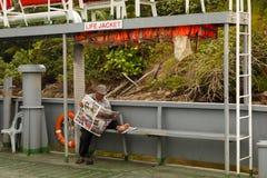 盖帽的人读一张报纸 免版税库存照片