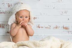 盖帽的女婴享受屋子的温暖的 库存图片