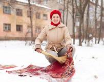 盖帽的妇女清洗地毯与雪 免版税库存照片